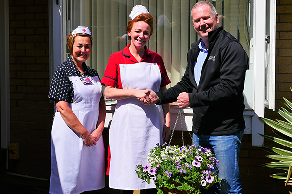Dylan James (AP Broome Senior Manager) presenting 2 hanging baskets to the Matron of Intermediate Care Service Kate Myatt (in Red) and left of the picture is Lee Cantliff, both in period uniform.